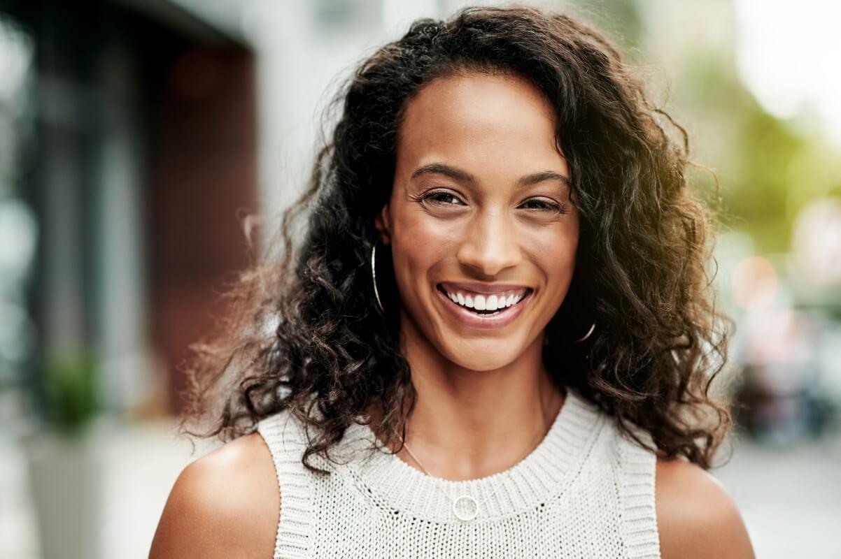 Lachende attraktive Frau mit gesunden, natürlich weißen Zähnen
