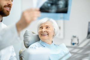 Fröhliche, ältere Patientin mit gesunden Zähnen bei der Vorsorge