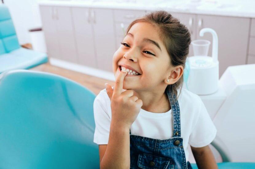 Lachendes, fröhliches Kind auf dem Behandlungsstuhl zeigt stolz seine Zähne