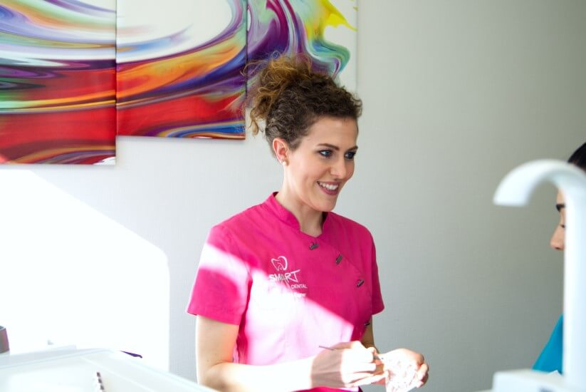 Zahnärztin Julia Eigner, lächelnd bei der Erklärung eines Themas an eine Teamkollegin